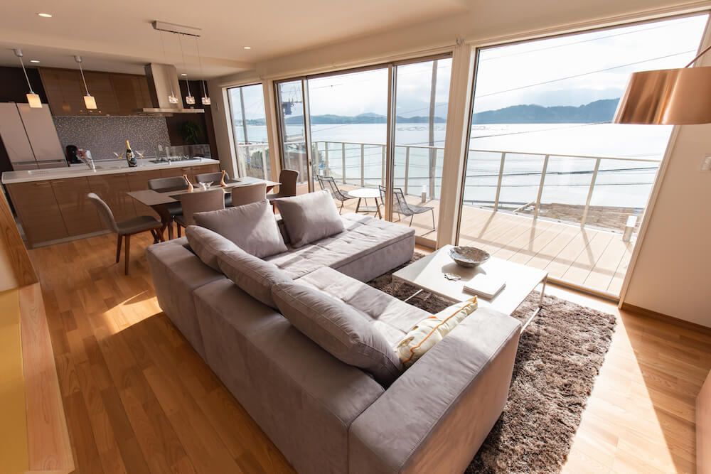 糸島の海が見える家のバルコニーとリビングルーム